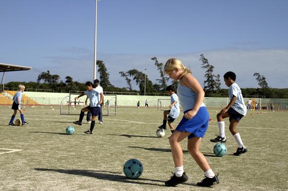niños y niñas jugando al fútbol